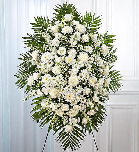 All-white standing spray arrangement with roses, football mums, cremones, stock, snapdragons, carnations, daisy poms and monte casino; accented with soft, lush greenery