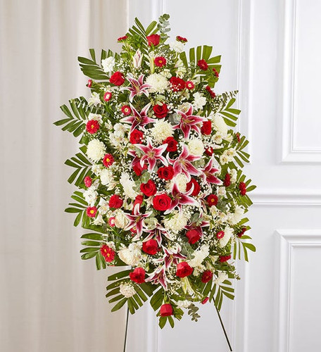 One-sided standing spray arrangement with red roses, pink Stargazer lilies, white Peruvian lilies (alstroemeria), carnations and football mums; accented with spiral and seeded eucalyptus, baby's breath and assorted greenery