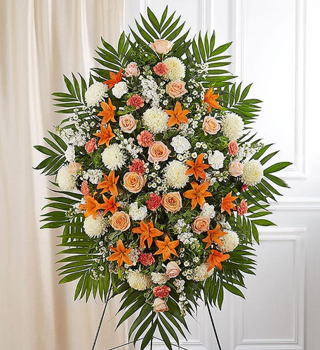 One-sided standing spray arrangement with roses, orange Asiatic lilies and carnations, white football mums, stock, carnations and monte casino; accented with assorted greenery