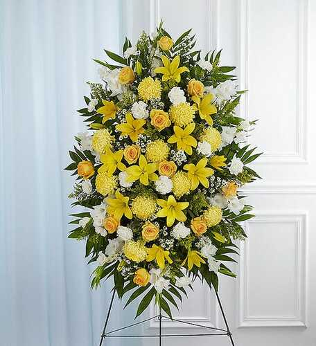 Standing spray arrangement with yellow roses and daisy poms; white yellow Asiatic lilies , gladiola, yellow football mums , carnations and monte casino; accented with soft, lush greenery