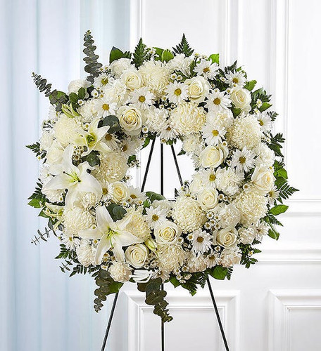 All-white standing wreath arrangement with roses, football mums, stock Oriental lilies, carnations, daisy poms and monte casino; accented with soft lush greenery