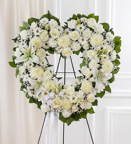 Open, heart-shaped arrangement of all white roses, hybrid lilies, football mums, carnations and daisy poms; accented with baby's breath and soft, lush greenery
