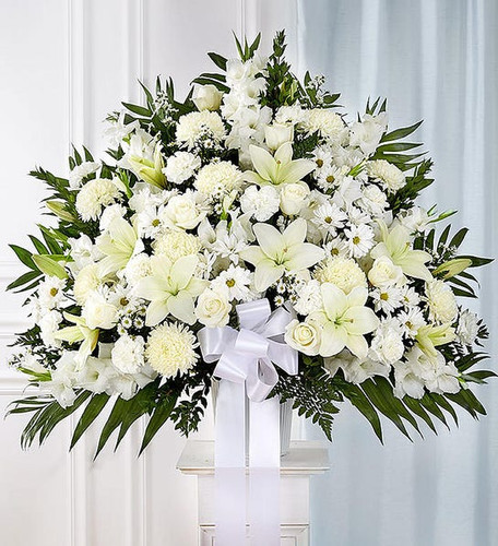All-white standing basket arrangement with roses, Asiatic lilies, football mums, gladiola, carnations, daisy poms and monte casino; accented with soft, lush greenery and white bow