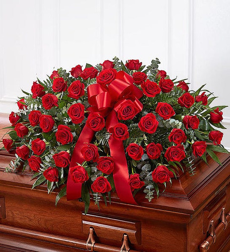 Half casket cover arrangement of red roses and fresh greenery; accented with a red satin ribbon