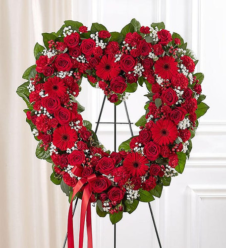 All-red open heart-shaped arrangement of roses, spray roses, Gerbera daisies, carnations, mini carnations, hypericum; accented with baby's breath and soft, lush greenery