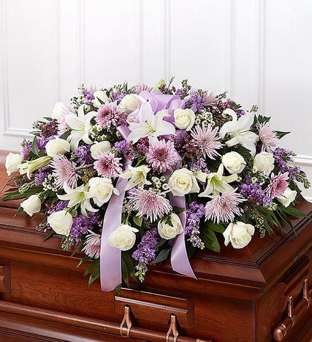 Half casket cover arrangement of white roses, lilies and monte casino, lavender cremones, spider mums and stock,  waxflower and fresh greenery; accented with a lavender satin ribbon
