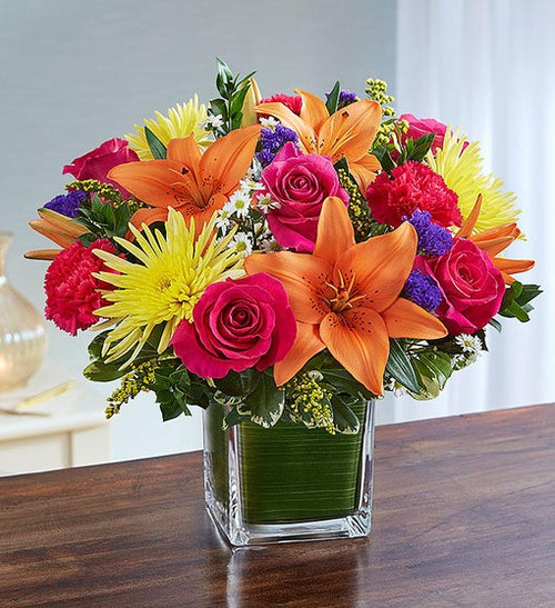 This arrangement of sprightly pink roses, carnations, orange lilies and yellow mums, expertly gathered together in a clear glass cube lined with a Ti leaf ribbon, is an uplifting gift of comfort and hope.