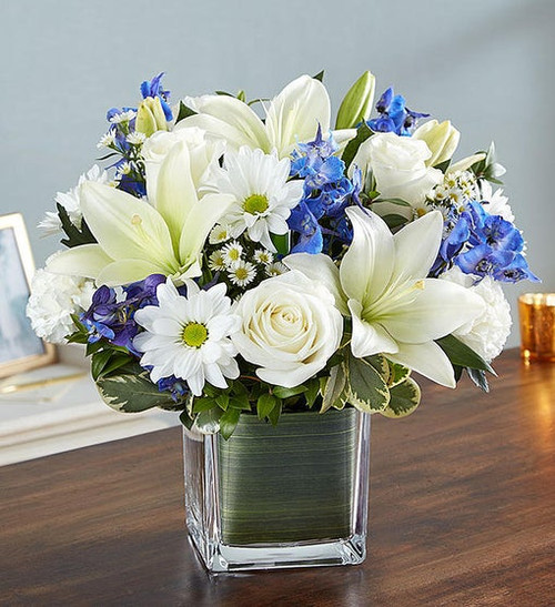 Ocean serenity of blue and white. Our arrangement of fresh blue delphinium, white roses and lilies, expertly gathered together in a clear glass cube lined with Ti leaf ribbon, makes for an exquisite gesture.