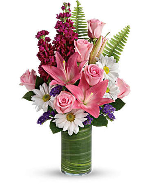 White daisies, pink lilies and fuchsia stock is a fun surprise for any special occasion! It's wrapped in a ti leaf in a glass cylinder vase for a modern touch.Pink asiatic lilies, pink roses, fuchsia stock, white daisy spray chrysanthemums, and statice are accented with sword fern, variegated ti leaf, and leather leaf.