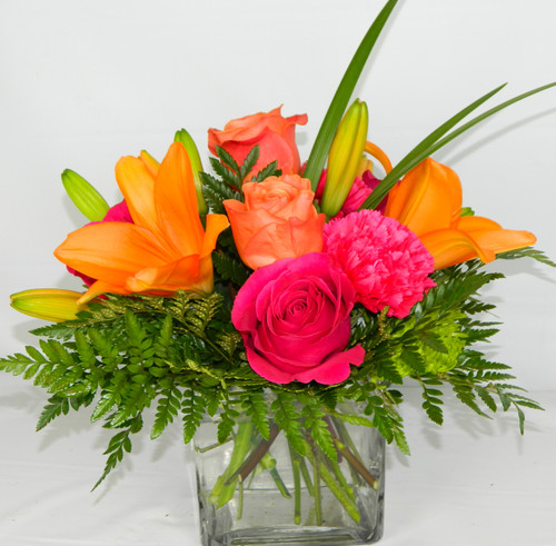 Caribbean hot pinks and oranges are contrasted by the cool clarity of a simple cube vase. An eye-catching everyday choice!Orange Asiatic lilies, hot pink and light orange roses, miniature red carnations and a bit of understated greenery.