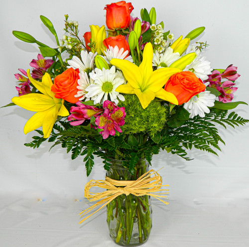 All-around arrangement with orange roses; yellow Asiatic lilies; pink Peruvian lilies (alstroemeria); green trick; white daisy poms; accented with greens and wax flowers