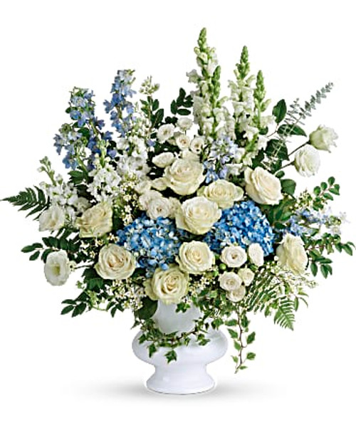 blue hydrangea, white roses, white spray roses, white lisianthus, light blue delphinium, white snapdragons, white stock, and white wax flower is accented with huckleberry, variegated ivy, spiral eucalyptus, dagger fern, and lemon leaf