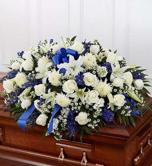 Half casket cover arrangement of white roses, hybrid lilies, football mums, monte casino and stock, blue delphinium and emerald; accented with a blue satin ribbon