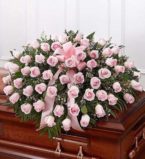 Half casket cover arrangement of pink roses, waxflower and fresh greenery; accented with a pink satin ribbon