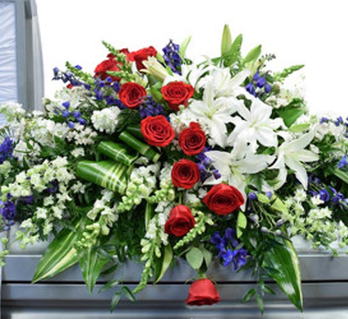 designed with blue delphinium, white larkspur, white lilies, white snap dragons, red freedom roses and variegated ti leaves.