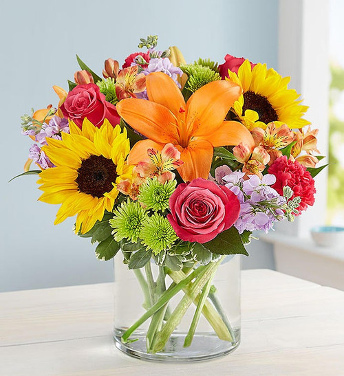 All-around arrangement of hot pink roses and carnations; orange Asiatic lilies and Peruvian lilies (alstroemeria); yellow sunflowers; lavender stock; Athos poms; accented with assorted greenery