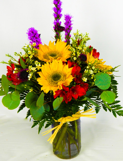 A flower bouquet that offers a way to bring Texas garden's beauty and light into their home, this gift is an expression of the colors and flowers you may encounter in Texas gardens. Bold yellow sunflowers catch the eye at every turn accented with red alstromeria, purple liatris, wax flower, and lush greens arranged artistically in a clear lavender glass jar that gives it a natural, rustic look they will love. A unique thank you, thinking of you, or get well gift!