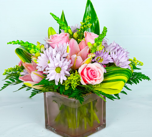 Our Victoria arrangement is nested in a pastel pink cube, it contains soft pastel colors with beautiful soft pink roses, daisies, asters, lilies, snaps and all hugged with variegated tea leaves, modern, unique and very Victorian, ready for just about any occasion.