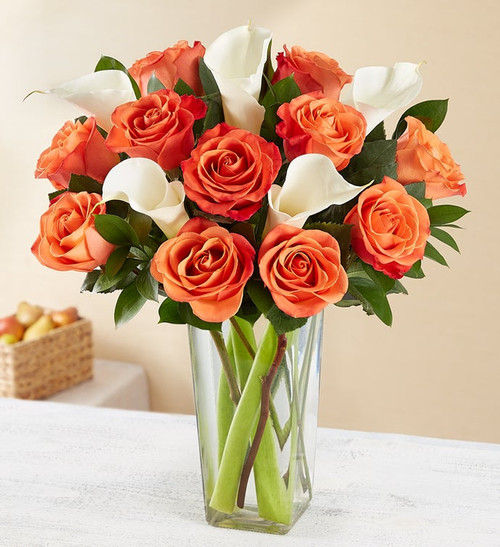Arrangement of 12 long-stem orange roses and 5 white Calla lilies, gathered with fresh greenery (shades of orange may vary)