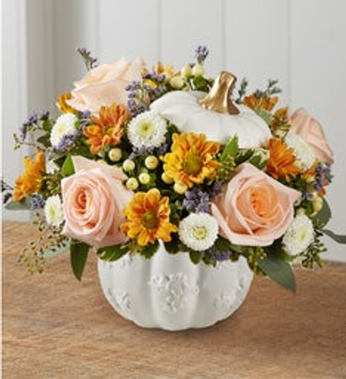 All-around arrangement with peach roses, white button poms, autumn-colored daisy poms and purple limonium; accented with cream hypericum, seeded eucalyptus and assorted greenery Artistically designed in our exclusive grateful white pumpkin, a modern-styled white satin finish container with lid and golden accents; this unique design that can be used for fresh flowers, wrapped candies or as a seasonal décor piece