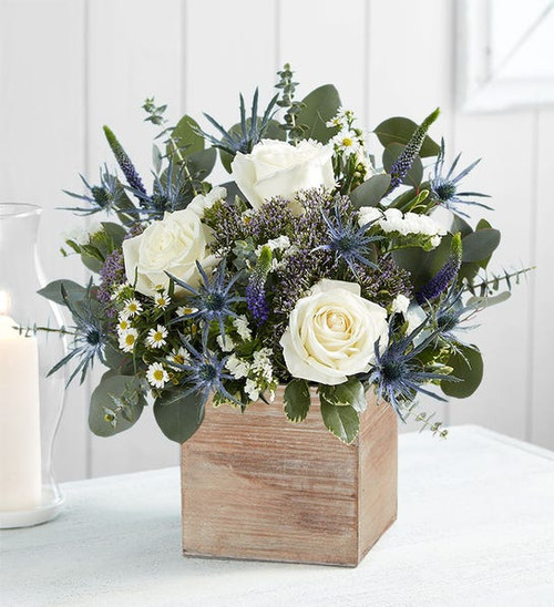 All-around arrangement with purple Veronica, white roses, monte casino and statice, blue thistle, purple trachelium; accented with spiral eucalyptus and assorted greenery