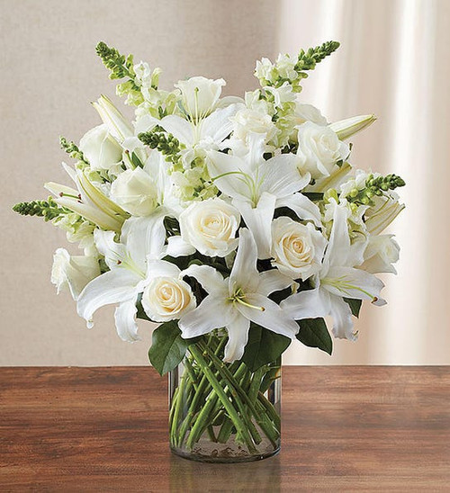 All-around arrangement with white roses, lilies and snapdragons; accented with greenery