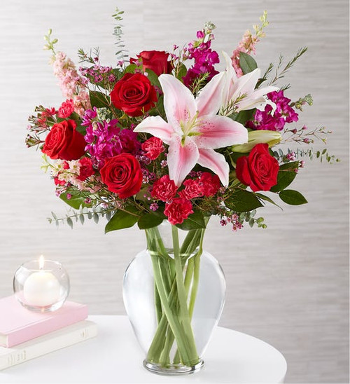 """All-around arrangement with red roses; pink Oriental lilies; stock;  mini carnations; purple waxflower; accented with spiral eucalyptus and assorted greenery Artistically designed in a glass garden vase; measures 11""""H"""