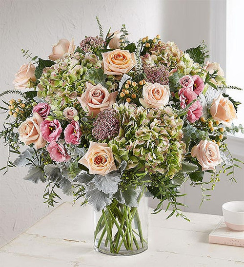 All-around arrangement with roses, antique hydrangeas, Veronica and accented with hypericum, rice flower, dusty miller, spiral eucalyptus and assorted greenery, colors and varieties may change on seasonal availability, always keeping the look, feel and value.