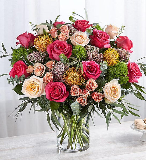 All-around arrangement with hot pink roses, spray roses and orange pincushion protea; accented with rice flower, spiral and feather willow eucalyptus and assorted greenery