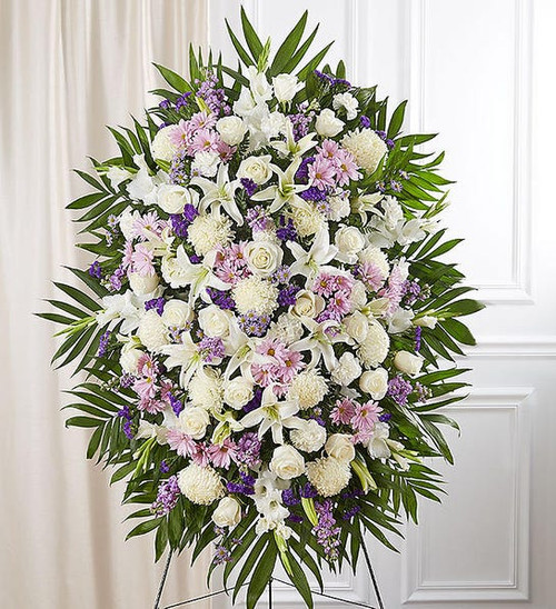 Standing spray arrangement with lavender daisy poms, stock and monte casino; white roses, Oriental lilies, football mums, gladiola and carnations; purple statice; accented with soft, lush greenery
