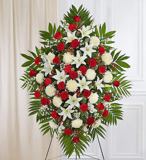 One-sided standing spray arrangement with red roses, carnations and hypericum, white Asiatic lilies, football mums, stock and monte casino; accented with assorted greenery