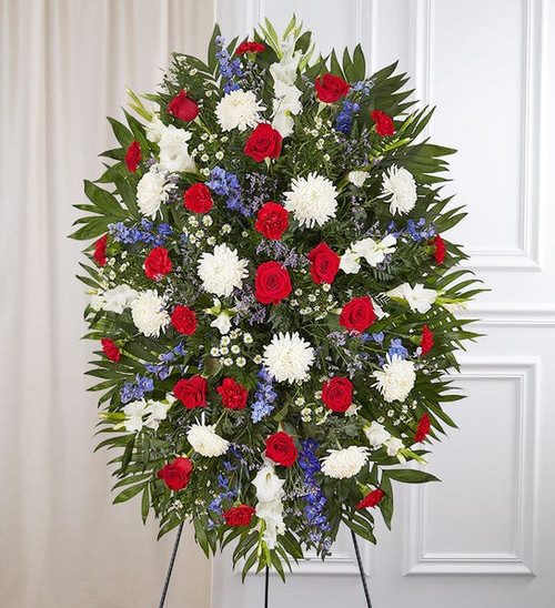 Standing spray arrangement with red roses and carnations; white football mums, gladiola and monte casino; blue delphinium; purple limonium; accented with soft, lush greenery