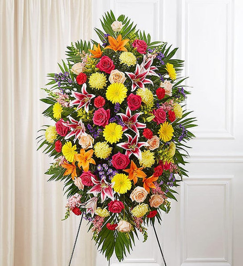 One-sided standing spray arrangement with red carnations, orange Asiatic lilies, yellow Gerbera daisies and football mums, peach and hot pink roses, pink Stargazer lilies and snapdragons, purple statice and monte casino; accented with assorted greenery