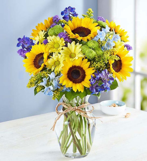 All-around arrangement with sunflowers, blue delphinium, yellow daisy poms, green button poms and purple statice, accented with assorted greenery