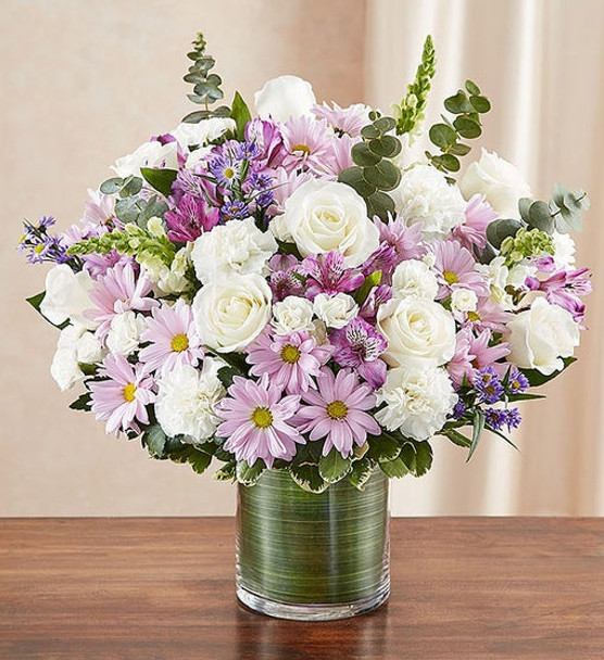 Our beautiful lavender and white sympathy arrangement filled with graceful lavender roses, alstroemeria and carnations, elegantly designed by hand in a graceful cylinder vase,