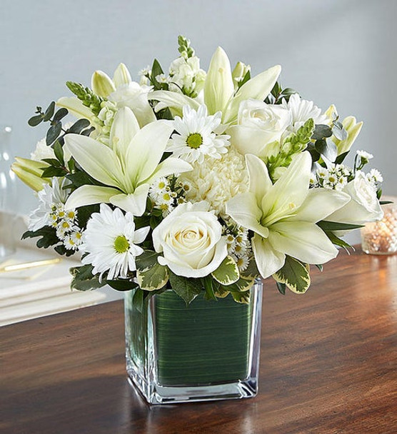 Our arrangement of angelic white roses, lilies, mums, daisy poms and more, expertly arranged in a clear glass cube lined with a Ti leaf ribbon, makes for an exquisite gesture of comfort and healing.