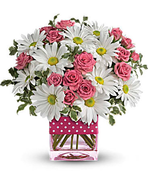 White daises hot pink roses in a glass cube vase adorned with a polka dot print ribbon.