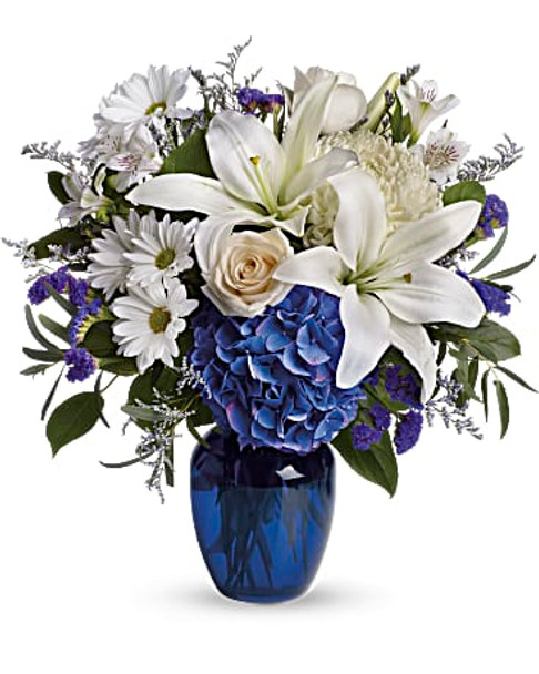 Blooms such as blue hydrangea, crème roses, graceful white oriental lilies, white alstroemeria, a white disbud mum, purple statice and lavender limonium are accented by seeded eucalyptus and salal in a stunning cobalt blue glass vase.