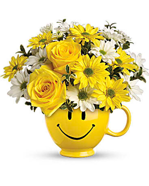 Yellow roses and daisy spray along with white daisy spray and leather leaf are delivered in a smiley face mug.