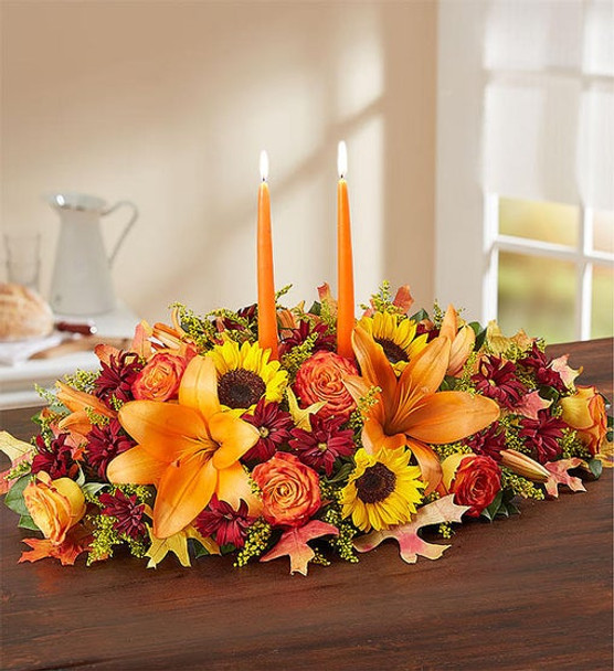 All-around centerpiece arrangement with autumn-colored roses, sunflowers, red daisy poms, orange Asiatic lilies, mini carnations and solidago; accented with assorted greenery and dried oak leaves
