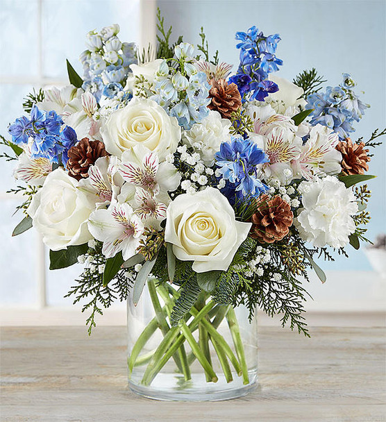 All-around arrangement with white roses, carnations, and Peruvian lilies (alstroemeria); blue delphinium; accented with baby's breath, seeded eucalyptus, assorted Christmas greenery, and pinecones