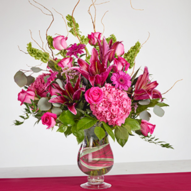 Sumatra or Stargazers lilies, hot Pink Floyd roses, lovey hydrangeas, Gerber daisies and Bells of Ireland in a bed of diverse greenery and finished with Willow tips.