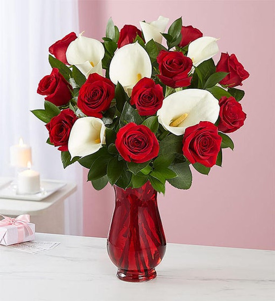 Gathering of long-stem red roses and white Calla lilies gathered with ruscus