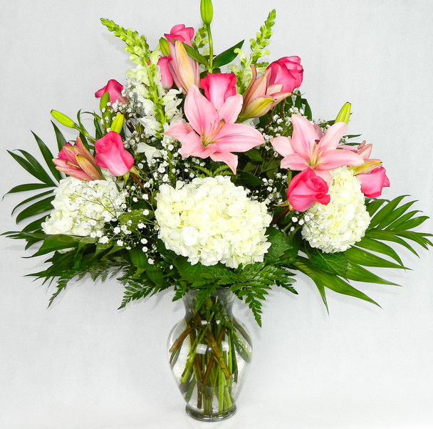A beautiful and Elegant arrangement to please them in any occasion. Pink tones sitting above the clouds of hydrangeas, roses, lilies, snapdragons, baby breath, assorted greenery in an illusion vase