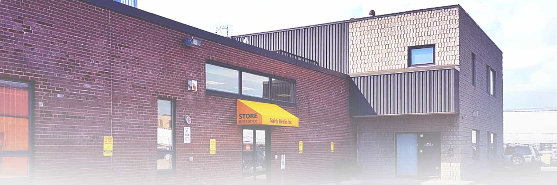 Safety Media Store Entrance: brick building with yellow sign reading 'Safety Media' overtop a glass door.