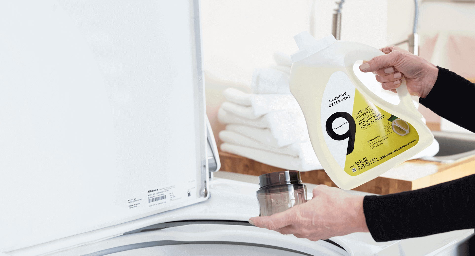 Person pouring Nine Elements Lemon Laundry Detergent into cap with bright white towels in the background.