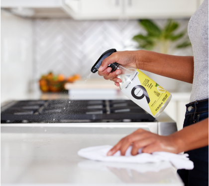 Woman spraying Nine Elements Lemon Multupurpose Cleaner on a shiny white countertop.