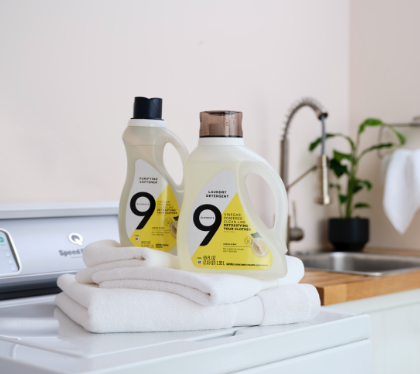 Nine Elements purifying softener and laundry detergent on top of bright white folded towels.