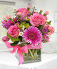 We have designed a perfectly pink arrangement using roses, mini carnations, Gerbera daisies, button mums and fillers with clear gemstones inside a cube vase with a lovely satin pink bow.