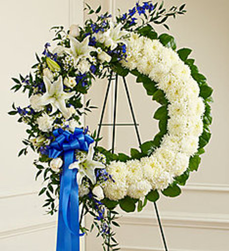"""•Standing wreath arrangement of fresh blue delphinium arranged with white roses, lilies, mums, carnations, monte casino and more •Accented by variegated pittosporum, ruscus and salal •Appropriate for family, friends and business associates to send directly to the funeral home •Our florists use only the freshest flowers available so colors and assortment may vary •Arrangement measures approximately 32""""H x 28""""W without easel"""